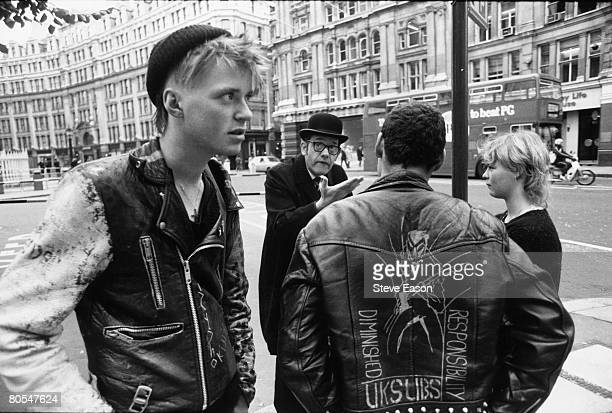 A bowlerhatted businessman argues with an anarchist on the back of whose jacket is written 'Diminished Responsibility UK SUBS' during the 'Stop the...