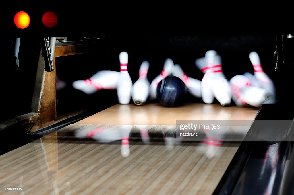 Strike: Bowling Ball Rolling Down Alley Lanes Hitting Pins