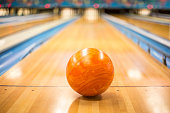 Close up view of an orange Bowling ball sitting in a colorful bowling alley lane