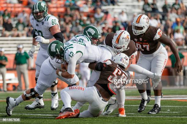 Bowling Green Falcons defensive lineman Malik Brown and Bowling Green Falcons linebacker Kholbe Coleman team up to tackle Ohio Bobcats quarterback...