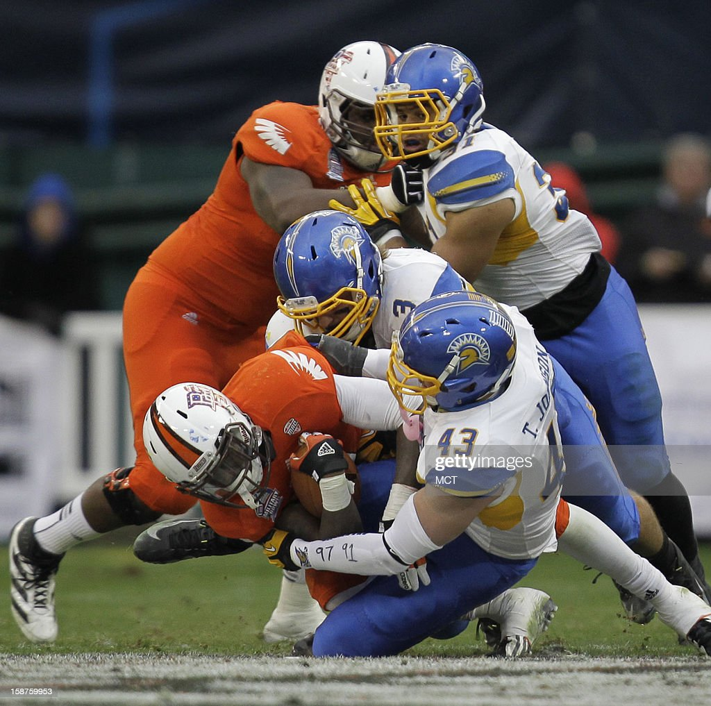 Bowling Green running back Anthon Samuel, left, is tackled by San Jose State defensive end Travis Johnson (43) and San Jose defensive tackle Travis Raciti (3) during the second quarter of the Military Bowl at RFK Stadium in Washington, Thursday, December 27, 2012. San Jose State defeated Bowling Green 29-20.