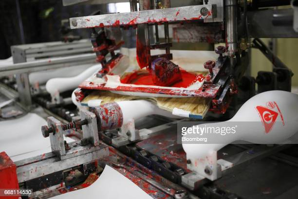 Bowling pins pass through a silk screen machine on an assembly line at the QubicaAMF Bowling Worldwide LLC facility in Lowville New York US on...
