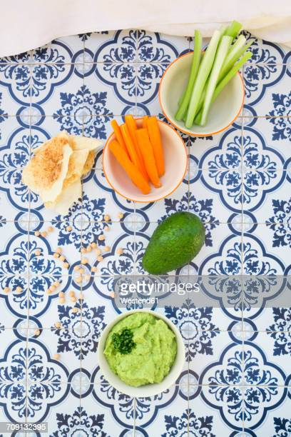 Bowls of avocado hummus and crudites, avocado, chick-peas and flat bread on tiles