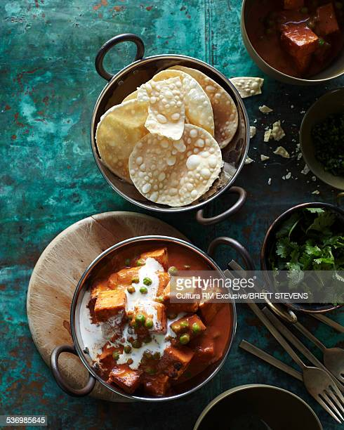 Bowls of balti mattar paneer and papadums