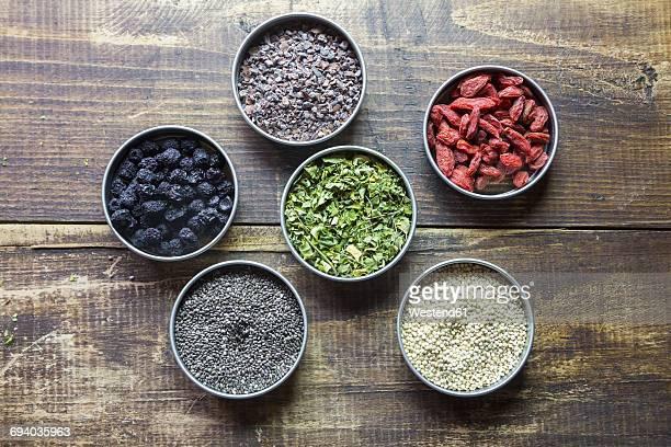 Bowls of chokeberries, chia, cocoa, quinoa, moringa and wolfberries