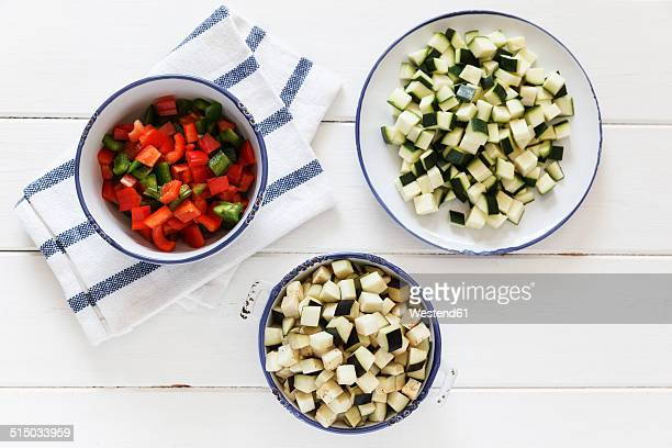 Bowls of diced red and green ball peppers, courgettes and eggplant on white wood, elevated view