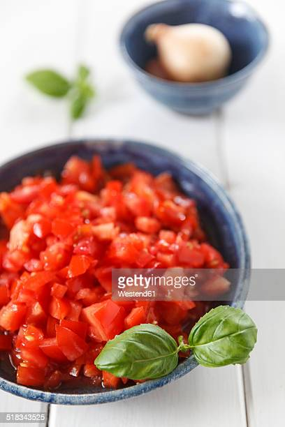 Bowls of diced tomatoes and onion on white wood