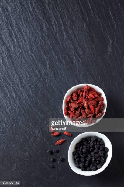 Bowls of goji and chokeberries on slate