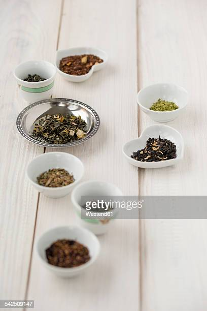 Bowls of various sorts of tea on white wood