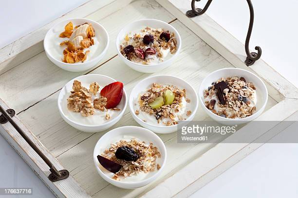 Bowls of yogurt with muesli and fruits on wooden tray