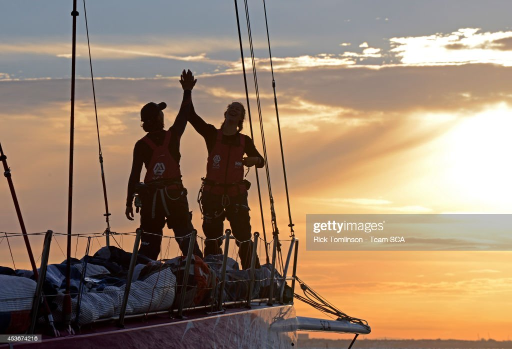 Bowman Sara Hastreiter (USA) and Sophie Ciszek (AUS) high five as Team SCA's Volvo Ocean 65 skippered by Sam Davies finishes at dawn, beating the all female round Britain record, during the Sevenstar Round Britain and Ireland Race 2014 off the Royal Yacht Squadron August 16, 2014 Cowes, Isle of Wight, England. Team SCA crossed the finish line of the 1880nm race at 06.10.39 BST on Saturday 16th August 2014 with an elapsed time of 4 days, 21 hours, 00 minutes and 39 seconds. This breaks the previous World Record for Women's Monohull set by Aviva, an Open 60, in 2009, by 1 day, 14 hours, 30 minutes and 14 seconds. SCA's record is subject to ratification by the World Speed Sailing Record Council. Among the women onboard SCA in 2014, both Dee Caffari and Sam Davies were also onboard Aviva when the World Record was set in 2009.
