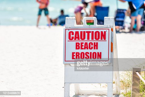 Bowman's beach at Sanibel Island with, many people, crowd in bokeh background, crowded coast, sand, caution erosion red sign closeup danger safety warning : Stock Photo