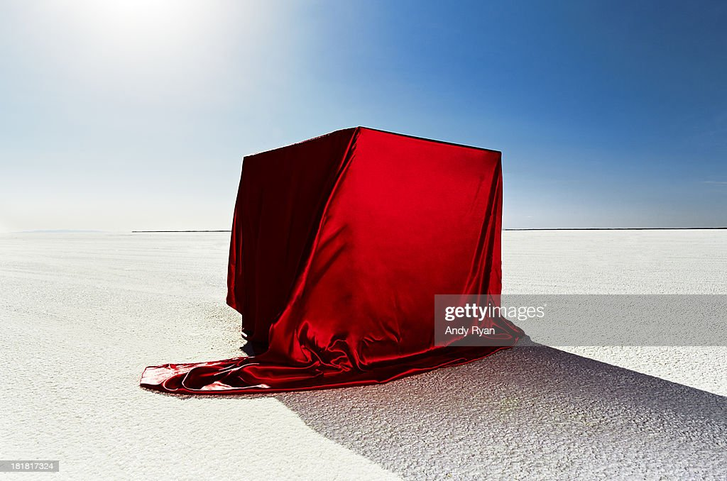 Box covered in red fabric on salt flats.