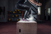 Young woman jumping box and talc powder departs from under feet. Fitness woman doing box jump workout at gym gym.
