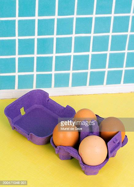 Box of four eggs on yellow kitchen counter by blue tiled wall
