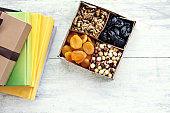 A box of nuts and dried fruits and a stack of books. Dried apricots, prunes, walnuts, hazelnuts.