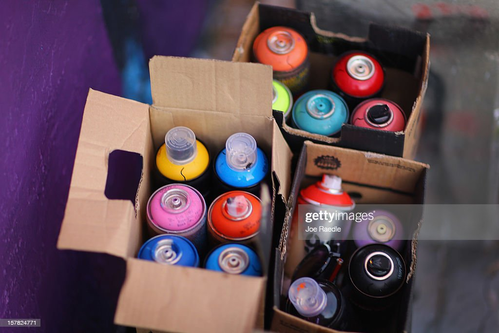 """A box of spray paint is seen as artists paint on the walls of buildings as they participates in the Wynwood Walls art project on December 6, 2012 in Miami, Florida. The art project along with many other satellite shows around the city coincide with the International art show, """"Art Basel"""", which runs until the 9th of December."""
