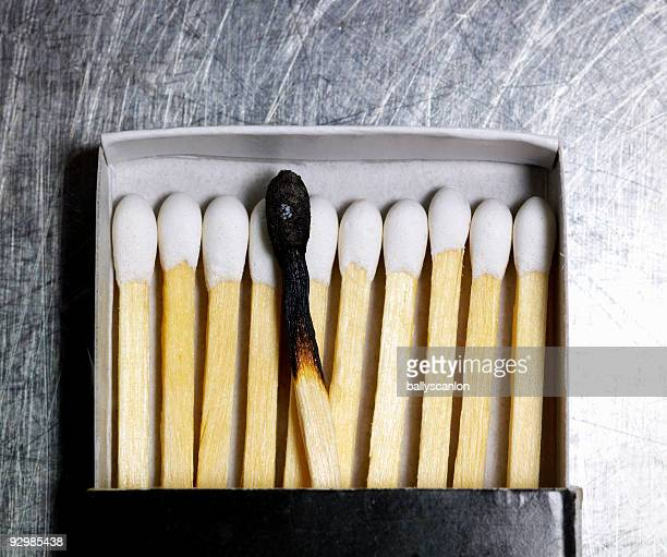 Box of wooden matches with one burned match.