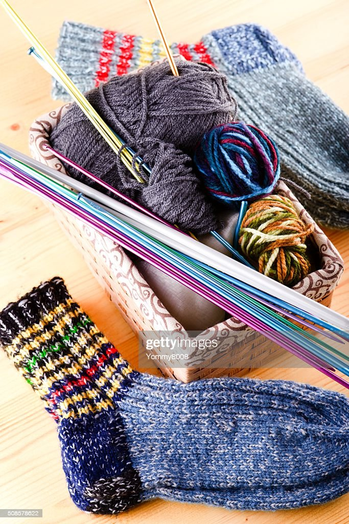 Box with knitting accessories and pair of socks : Stock Photo