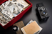 A box with family vintage photos on a table with a magnifying glass and a vintage camera next to it