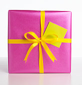 Box wrapped in purple paper and yellow ribbon, yellow gift tag