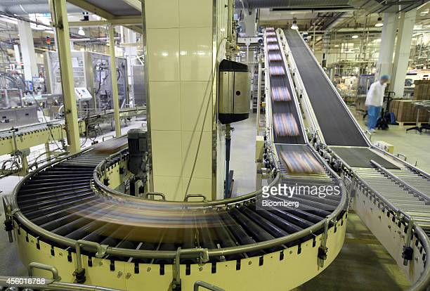 Boxed packages of yogurt cartons pass along a conveyor belt before packaging at the Group Danone in Russia dairy production plant operated by Danone...