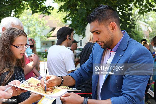 Boxer Amir Khan stops to sign an autograph during the parade at the International Boxing Hall of Fame induction Weekend of Champions events on June...