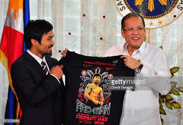 Boxer and congressman Manny Pacquiao gives President Benigno Aquino III a shirt and memorabilia following his win of the WBC super welterweight crown...