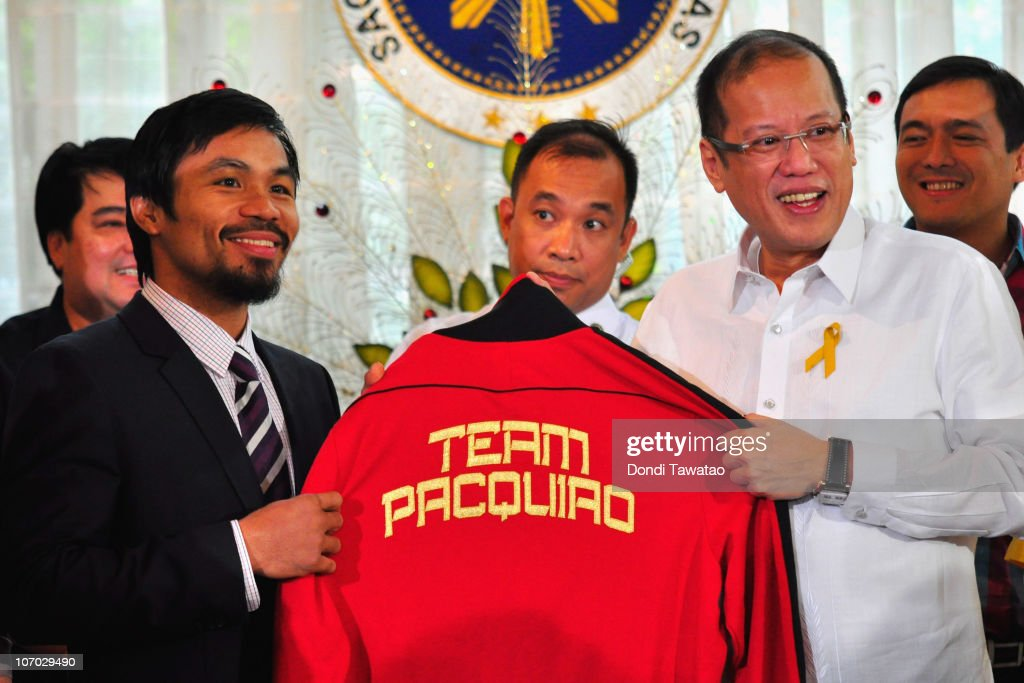 Boxer and congressman, Manny Pacquiao gives President Benigno Aquino III a shirt and memorabilia following his win of the WBC super welterweight crown against Mexican Antonio Margarito on November 20, 2010 in Manila, Philippines. Pacquiao, an icon in the Philippines, won his eigth world title against Mexican Antonio Margarito last week. Pacquiao is regarded as a hero in the country and is the first boxer to be elected to the House Representatives in the Philippines.