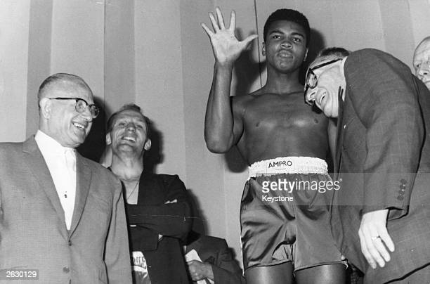 US boxer Cassius Clay and British boxer Henry Cooper weighin on the stage of the Palladium for their heavyweight match at Wembley Stadium London Ali...