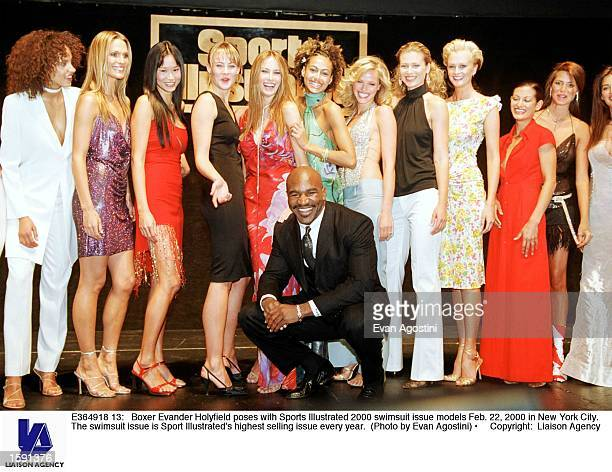 Boxer Evander Holyfield poses with Sports Illustrated 2000 swimsuit issue models Feb 22 2000 in New York City The swimsuit issue is Sport...