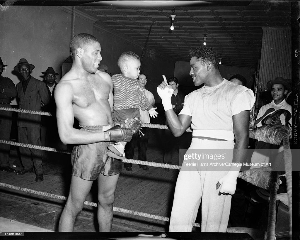 Boxer <a gi-track='captionPersonalityLinkClicked' href=/galleries/search?phrase=Ezzard+Charles&family=editorial&specificpeople=215068 ng-click='$event.stopPropagation()'>Ezzard Charles</a> pointing at baby held by another boxer, in boxing ring in Uptown Gym, Pittsburgh, Pennsylvania, February 1950.