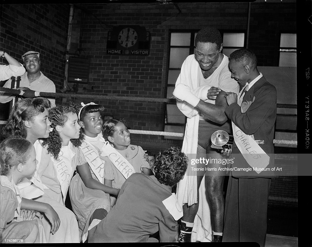 Boxer Ezzard Charles showing muscles to children wearing 'Cheers for Charles' sashes, including Ethel Holt, Jacqueline Holyfield, Chestina Mallory, Barbara Jackson, Ernestine Allen, Johnnie Allen, and Donald Smith, in Ligonier High School gymnasium, Ligonier, Pennsylvania, July 1951.