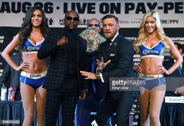 Boxer Floyd Mayweather Jr and UFC lightweight champion Conor McGregor pose as CEO of Mayweather Promotions Leonard Ellerbe looks on during a news...