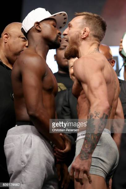 Boxer Floyd Mayweather Jr and UFC lightweight champion Conor McGregor face off during their official weighin at TMobile Arena on August 25 2017 in...
