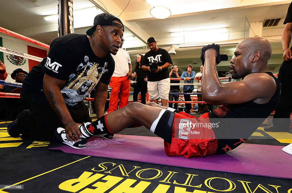 Boxer Floyd Mayweather Jr. (R) does sit-ups with his cousin and camp coordinator DeJuan Blake during a workout at the Mayweather Boxing Club on April 22, 2014 in Las Vegas, Nevada. Mayweather will face Marcos Maidana in a 12-round world championship unification bout in Las Vegas on May 3.