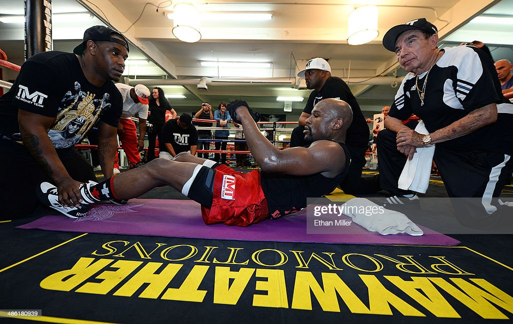 Boxer Floyd Mayweather Jr. (C) does sit-ups with (L-R) his cousin and camp coordinator DeJuan Blake, CEO of Mayweather Promotions Leonard Ellerbe and cornerman Rafael Garcia during a workout at the Mayweather Boxing Club on April 22, 2014 in Las Vegas, Nevada. Mayweather will face Marcos Maidana in a 12-round world championship unification bout in Las Vegas on May 3.