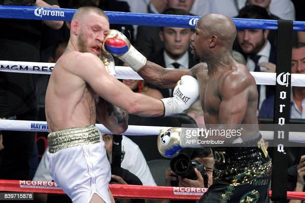 TOPSHOT Boxer Floyd Mayweather Jr lands a right to the face of mixed martial arts star Conor McGregor during their fight at the TMobile Arena in Las...
