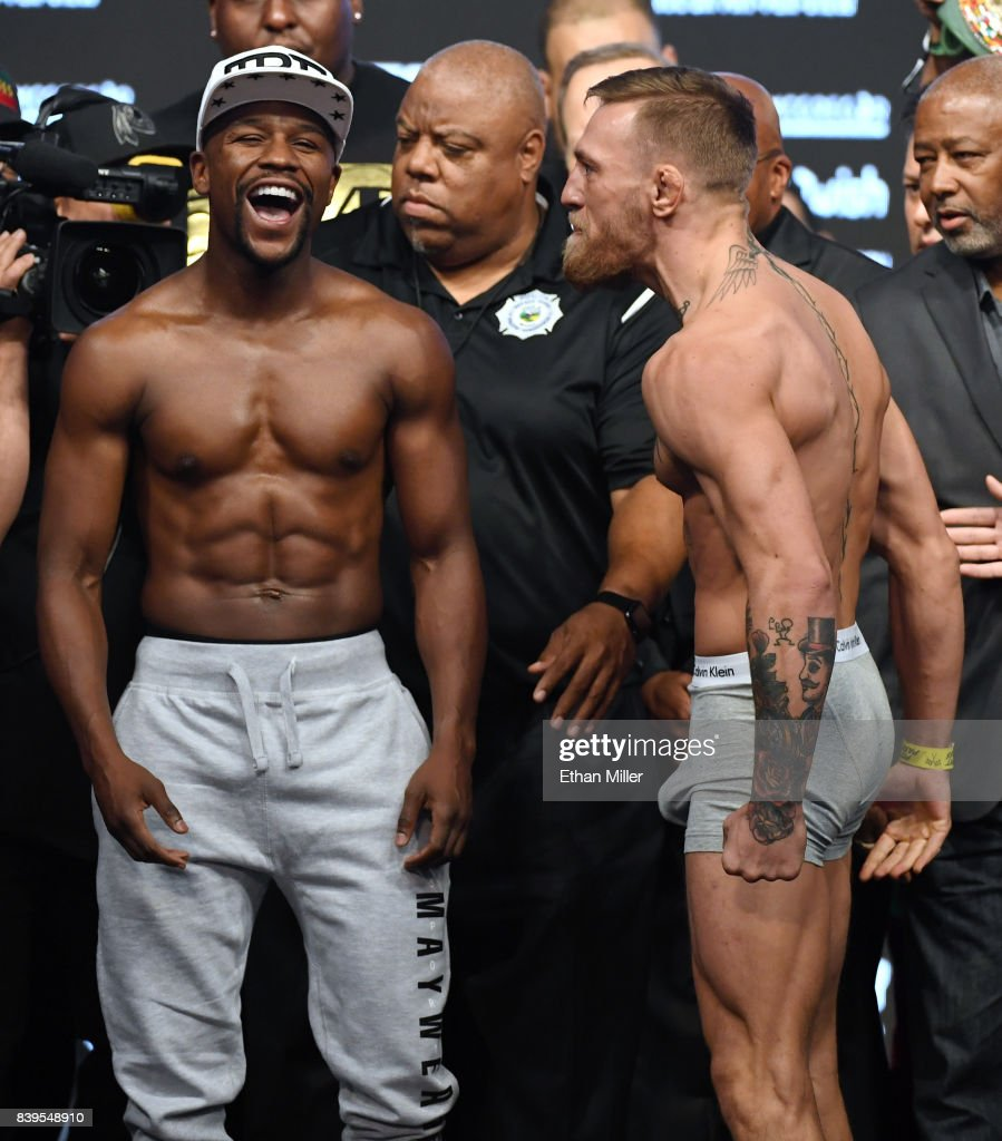 Boxer Floyd Mayweather Jr. (L) laughs after facing off with UFC lightweight champion Conor McGregor during their official weigh-in at T-Mobile Arena on August 25, 2017 in Las Vegas, Nevada. The two will meet in a super welterweight boxing match at T-Mobile Arena on August 26.
