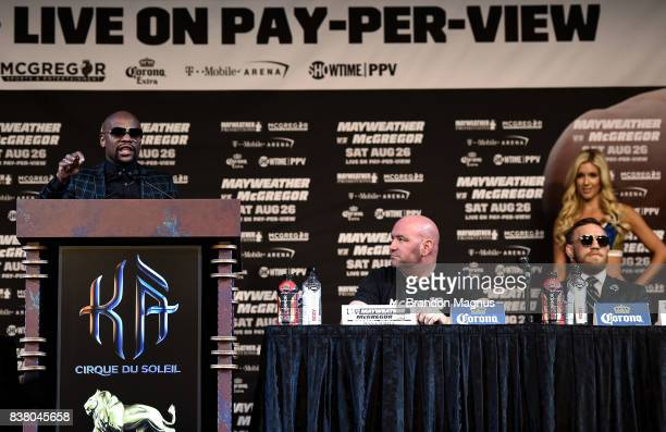 Boxer Floyd Mayweather Jr speaks to the media as UFC lightweight champion Conor McGregor sits during a news conference at the KA Theatre at MGM Grand...