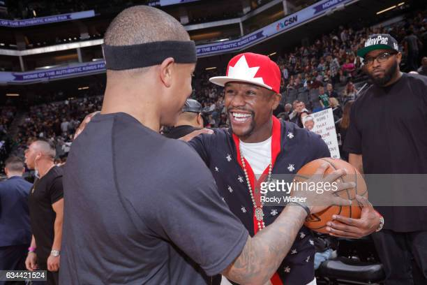 Boxer Floyd Mayweather talks with Isaiah Thomas of the Boston Celtics before the game against the Sacramento Kings at Golden 1 Center on February 8...