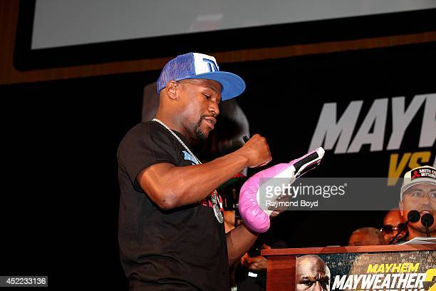 Boxer Floyd 'Money' Mayweather Jr signs autographs for fans during the 'Mayhem Mayweather vs Maidana II' championship rematch press conference at the...