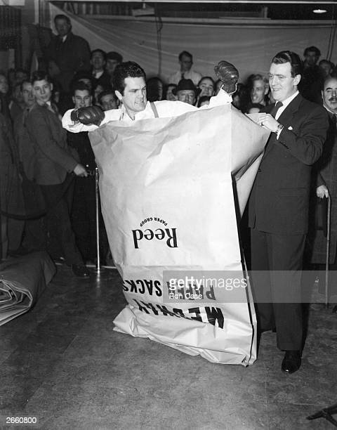 Boxer Freddie Mills tries to punch his way out of a paper bag at the National Packaging Exhibition Eamon Andrews is standing beside him
