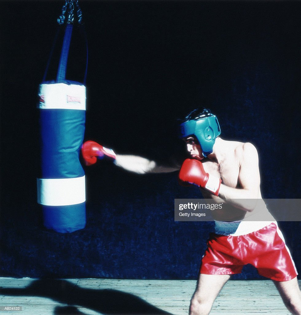 Boxer hitting punching bag : Stock Photo