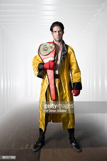 Boxer in robe posing with championship belt