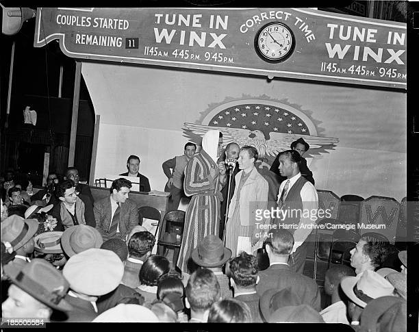 Boxer Joe Louis in striped robe and towel talking to two men at WINX microphone on stage with painted eagle on back wall in hall with audience in...