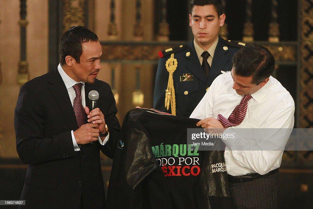 Boxer Juan Manuel Marquez and the president of Mexico Enrique Pena Nieto show a shirt at Palacio Nacional on December 14, 2012 in Mexico City, Mexico.