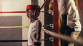 Kid wearing boxing gloves and headgear standing in a corner of a boxing ring. Small boy standing inside a boxing ring with his coach behind him.