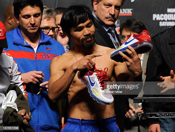 Boxer Manny Pacquiao appears on stage and points to his NIKE shoes during the official weighin for his bout against Juan Manuel Marquez at the MGM...
