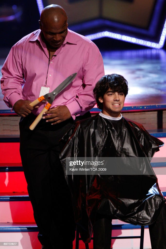 Boxer <a gi-track='captionPersonalityLinkClicked' href=/galleries/search?phrase=Mike+Tyson&family=editorial&specificpeople=194986 ng-click='$event.stopPropagation()'>Mike Tyson</a> cuts Musician Joe Jonas' hair onstage during the 2009 Teen Choice Awards held at Gibson Amphitheatre on August 9, 2009 in Universal City, California.
